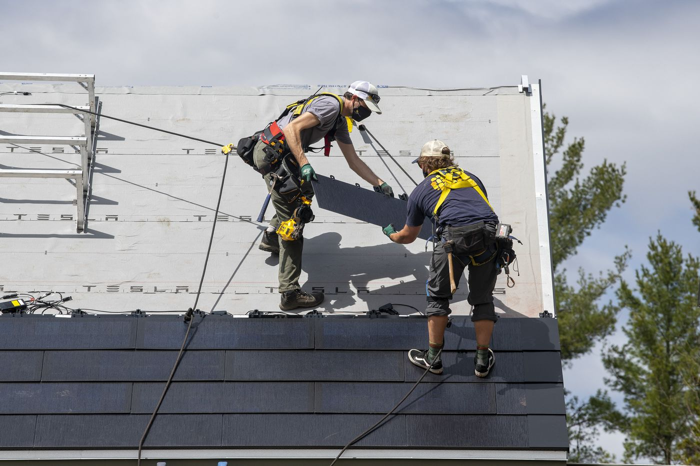 A crew installs Tesla solar shingles on an addition at Dan Reicher's home in Warren, Vt., April 13, 2021. (Caleb Kenna/The New York Times)