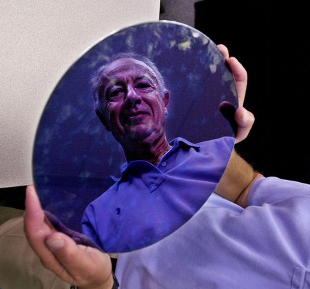 Former CEO and current Chairman of the Board of Intel Corp. Andy Grove is reflected in Intel's latest 300mm wafer, at Intel headquarters in Santa Clara, Calif., Thursday, June 26, 2001. Twenty years ago IBM turned to Intel for chips for it's first  PC's. (AP Photo/Paul Sakuma)
