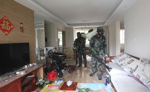 Military personnel decontaminate a home near the warehouse explosion site in Tianjin, China on Tuesday. Photographer: Wang Haobo/Xinhua/Getty Images