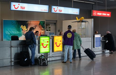 Passengers stand at the TUI Fly low-cost airline check in desk.