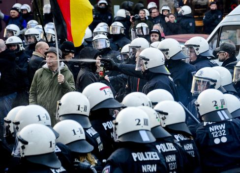 Police use pepper spray to control supporters of Pegida, Hogesa and other right-wing populist groups as they protest against the New Year's Eve sex attacks on Saturday.