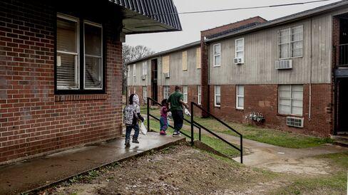 Children walk through the courtyard at the Warren Apartments.