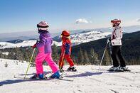 Family skiing time, winter activity, scenery, Baisoara Ski resort, Romania.