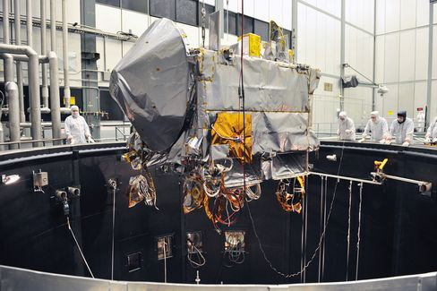 The OSIRIS-REx spacecraft being lifted into the thermal vacuum chamber at Lockheed Martin for environmental testing.