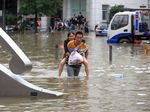 People walk through floodwaters in Zhengzhou, China onJuly 21.