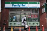 A pedestrian walks past a closed FamilyMart Co. convenience store in the Asakusa district of Tokyo, Japan.