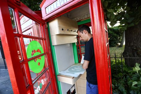 Alex Perjescu, co-founder and chief technical officer of Lovefone, applies decals to a phone box on Greenwich High Road in London.