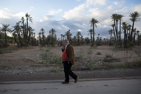 Jean-Yves Ollivier uses a mobile phone as he walks along a road near his property in Marrakesh, Morocco, on Dec. 1, 2014.