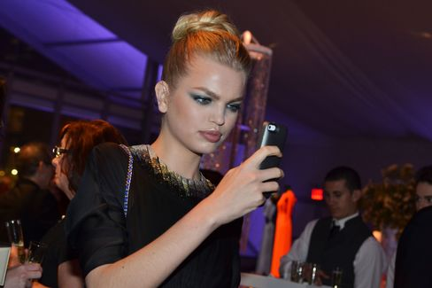 Model Daphne Groeneveld takes a picture of a friend at ABT's gala. Photographer:  Amanda Gordon/Bloomberg