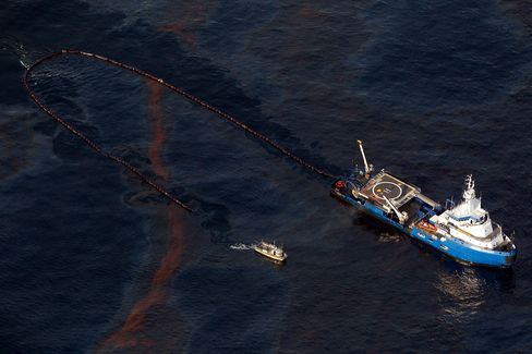 A boat works to collect oil leaked from Deepwater Horizon