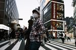 Pedestrians wearing protective masks cross a road in the Shinjuku district of Tokyo, Japan.
