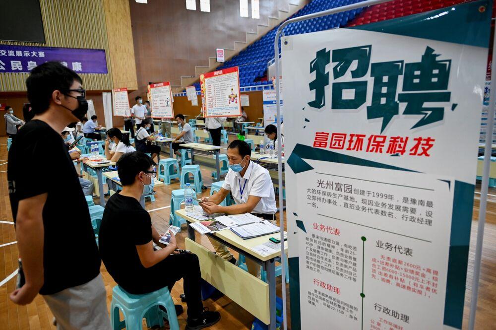 A job seeker talks with a human resource official at a job fair in Zhengzhou, July 2020.