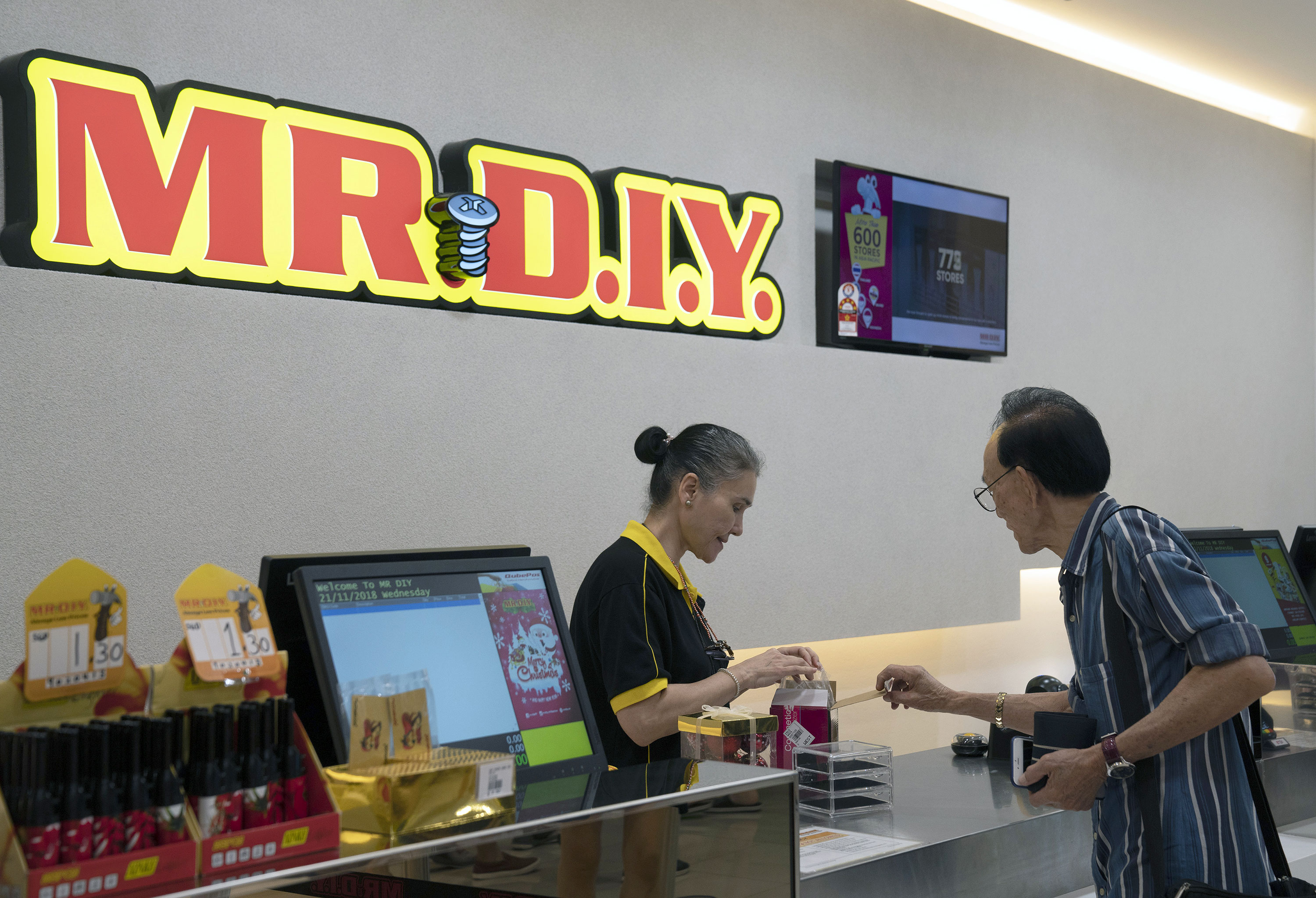 An employee assists a customer at Mr. DIY Sdn. hardware store in Singapore,