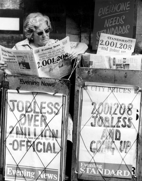 A newspaper seller reads the headlines proclaiming unemployment in Britain has overtaken the two million mark in August 1980.