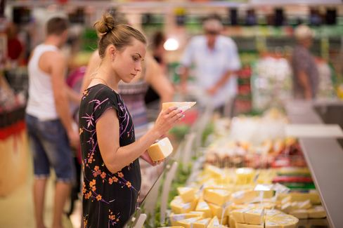 A customer checks the prices of slices of cheese inside an OAO Magnit hypermarket in Krasnodar, Russia, on Thursday, Aug. 7, 2014.