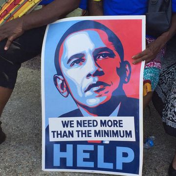 Supporters at a Bernie Sanders rally for a higher minimum wage carried a revised version of an iconic Obama campaign poster.