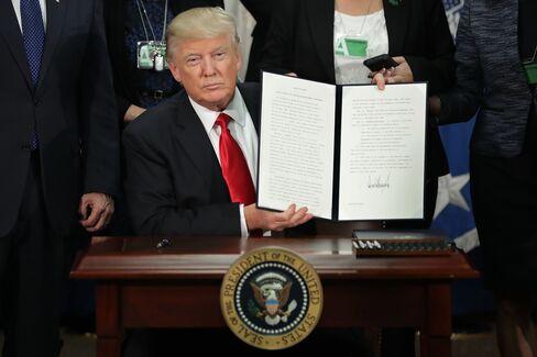 国土安全保障省で署名した大統領令を掲げるトランプ氏 (25日)