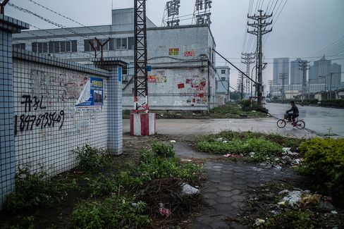 A man rides a bicycle at an abandoned industrial area in Dongguan, China. The country set a range for its economic growth target for the first time in two decades,The new goal comes at a precarious time as policy makers battle the slowest growth in 25 years, the yuan dropping to a five-year low and the second bear market in stocks in less than a year.
