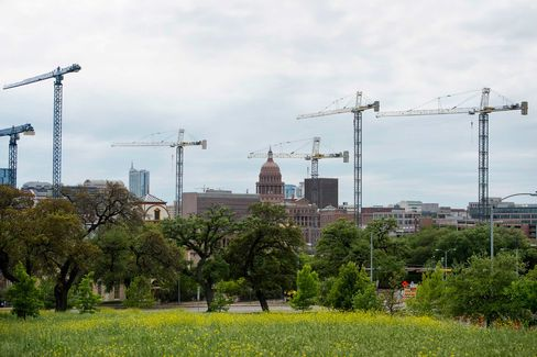 The Texas State Capitol building stands beyond construction cranes at the University of Texas at Austin campus in Austin, Texas, on April 4, 2015. About 900,000 people live in the city of Austin and that number is expected to reach nearly 1.3 million by 2040, a 40 percent increase, according to city figures. More than 100 people move to the city a day, according to the city's demographer.