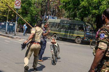 A police personnel beats a man with his stick during a government-imposed lockdown in Siliguri, India.