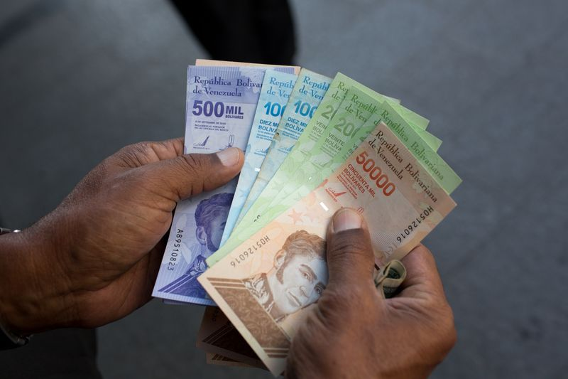 A person holds a new 500,000 bolivar banknote beside old 10,000, 20,000 and 50,000 bolivar banknotes outside a bank in Caracas, Venezuela, on Monday, March 15, 2021.