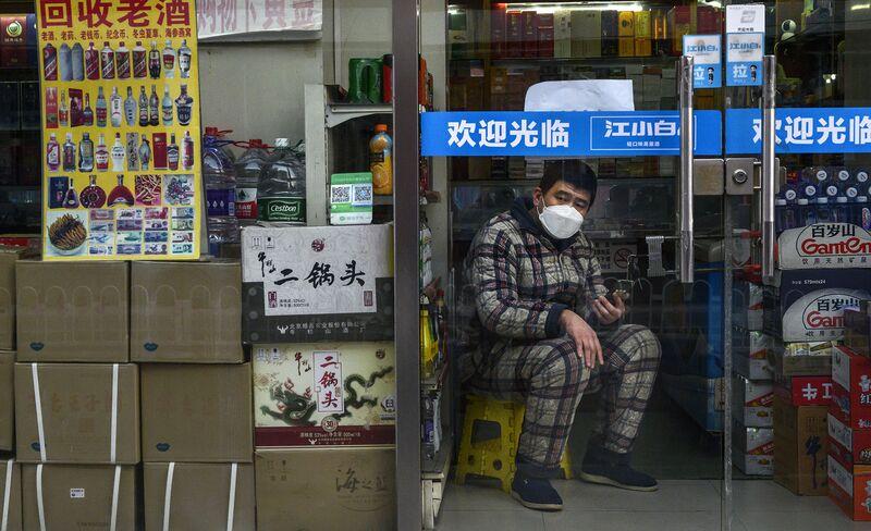 Un uomo attende i clienti nel suo negozio a Pechino il 25 febbraio.