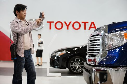 A visitor takes a photograph of a Toyota Motor Corp. Tundra truck on display at the company's Mega Web showroom in Tokyo, Japan, on Tuesday, May 5, 2015.