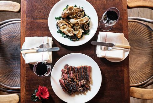 Galician beef sirloin served with onions, pickled walnut, pink fir potatoes, and Tunworth, a cow's-milk cheese, at Kitty Fisher's.