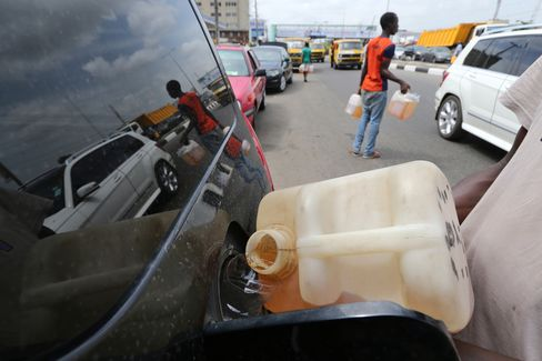 A man sells fuel to a motorist queuing to use a petrol station in Lagos on April 7.