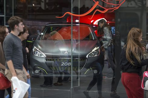 A Peugeot 208 automobile sits in a showroom in Paris.