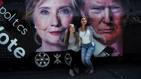 Students pose with a backdrop of Hillary Clinton and Donald Trump at Hofstra University in Hempstead, New York, on Sept. 26, 2016.