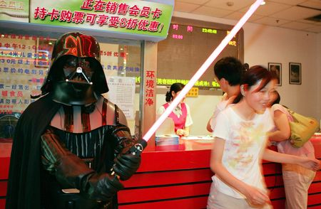 """A man dressed as Darth Vader from the movie """"Star Wars: Episode III - Revenge of the Sith"""" holds a light saber in a movie theatre May 19, 2005 in Chengdu of Sichuan Province, China."""