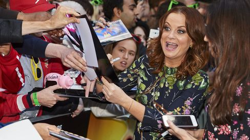 Actress Amy Poehler signs autographs ahead of a gala screening of the movie 'Inside Out' in central London on July 19, 2015.