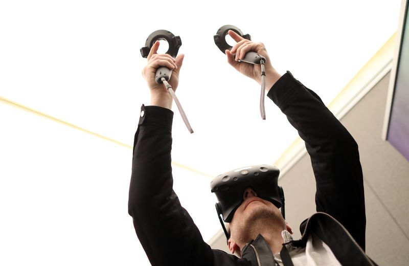 An attendee holds virtual control sticks whilst wearing a HTC Corp. Vive virtual reality (VR) headset at the Virtual Reality World Congress in Bristol, U.K., on Wednesday, April 12, 2017. Virtual reality proponents say that liberating computing from the confines of glass rectangles will change the way people interact with information. Photographer: Chris Ratcliffe/Bloomberg
