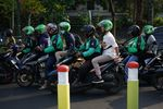 Riders and passengers on Go-Jek motorcycles in Jakarta.