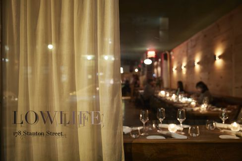 A peek into the candlelit dining room from Stanton Street.