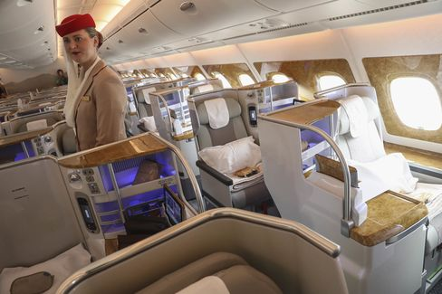 エミレーツ航空A380のビジネスクラス席で乗客を迎える乗務員
