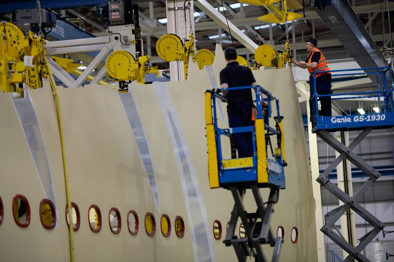 Employees work on a section of a wing on an Airbus A350