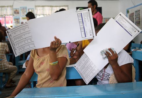 Voters cover their faces with ballots at the Hacienda Luisita plantation in Tarlac City, the Philippines in 2010.