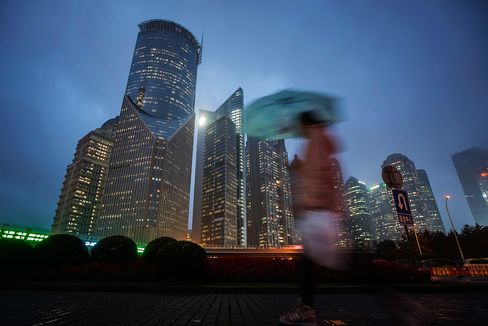 A pedestrian holding an umbrella walks past buildings illuminated at night in the Lujiazui district of Shanghai, China, on Thursday, Oct. 29, 2015.