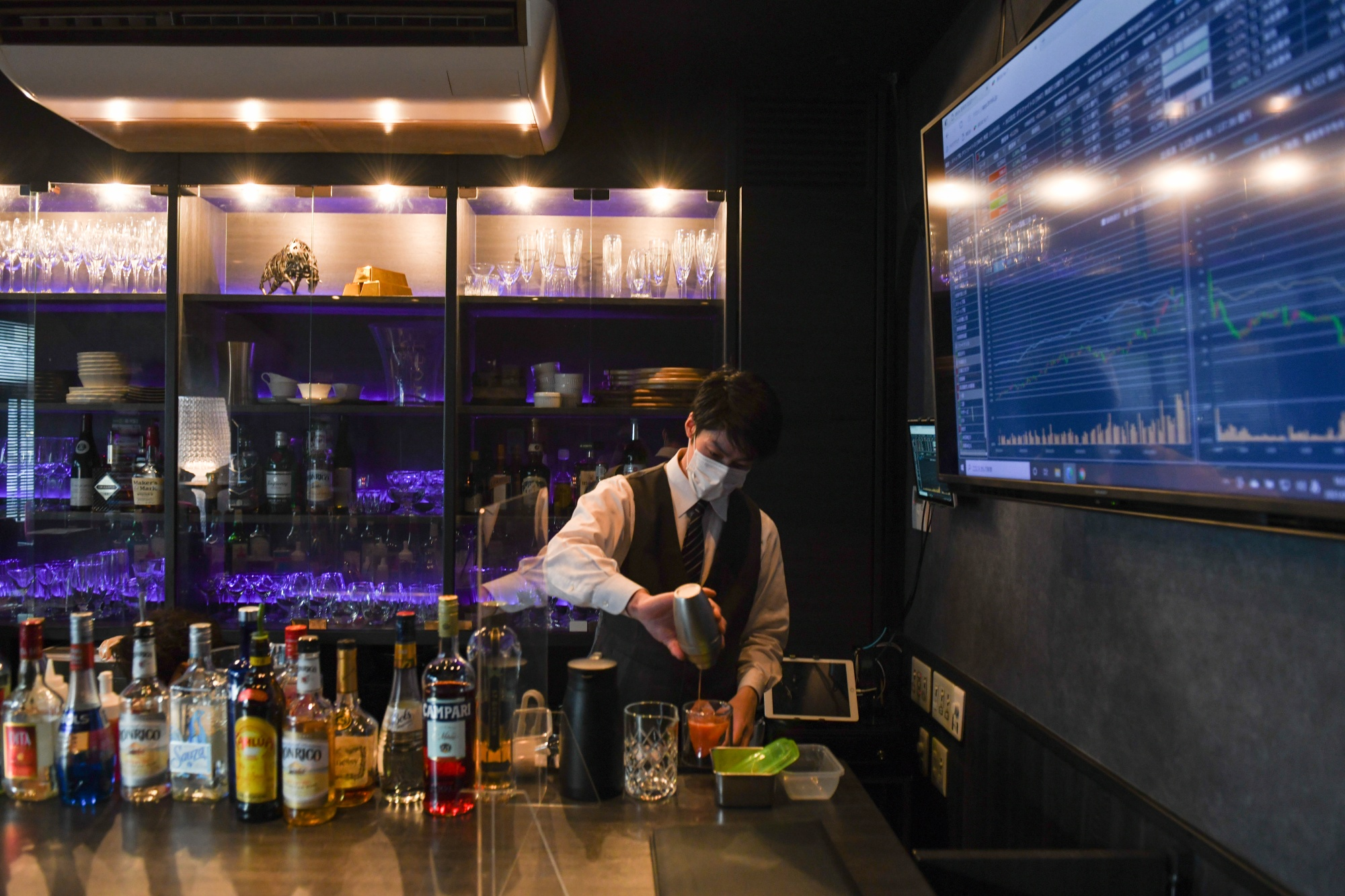 A bartender prepares drinks next to a screen displaying stock quotes and other financial information at Stock Pickers in Tokyo.