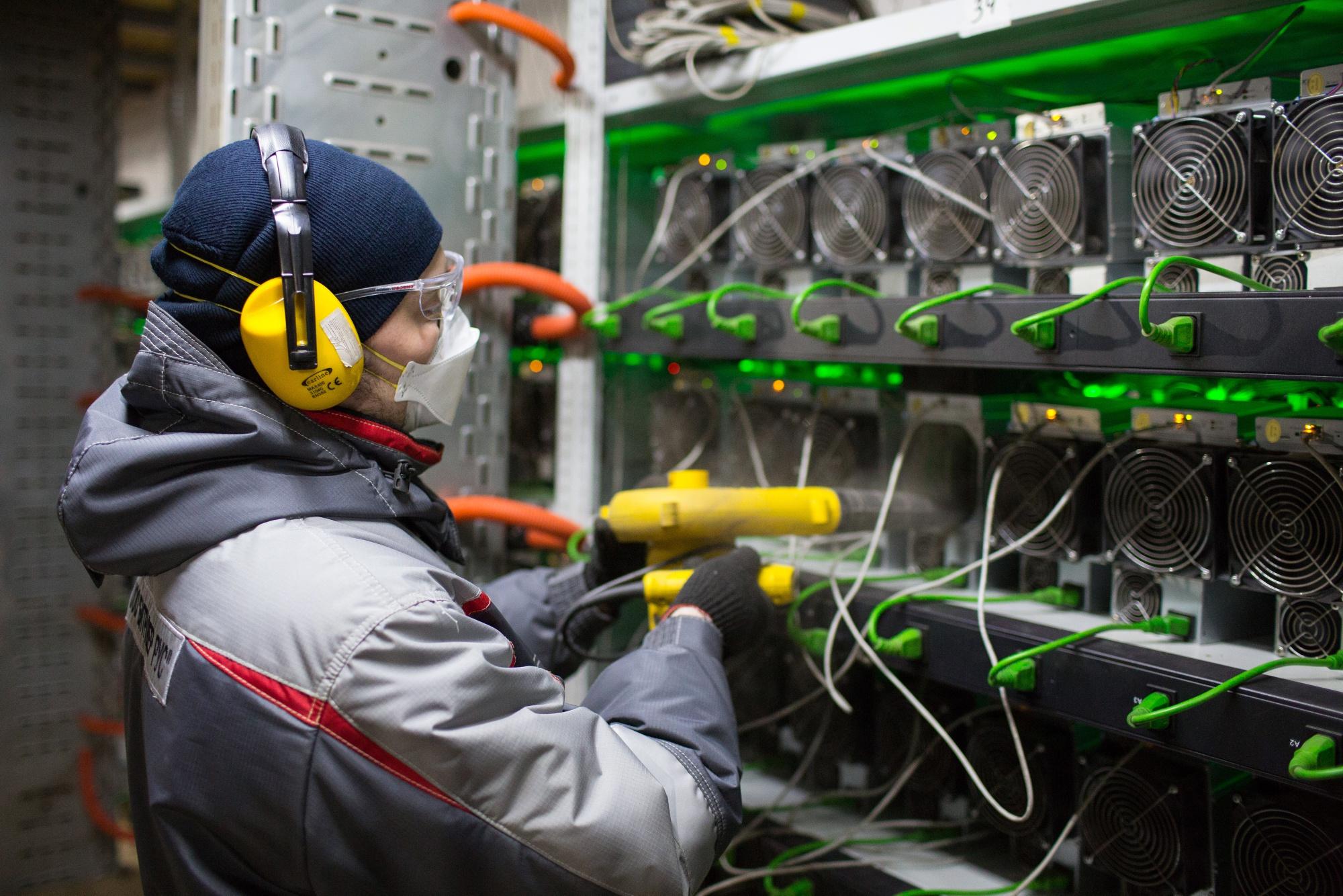 Seorang pekerja membersihkan unit di pertanian penambangan cryptocurrency.
