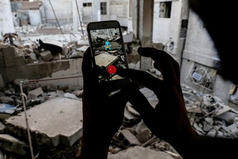 A Syrian gamer uses the Pokemon Go application on his mobile to catch a Pokemon amidst the rubble in the besieged rebel-controlled town of Douma, Syria.