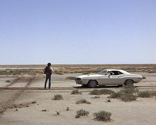 The fugitive Kowalski, played by American actor Barry Newman, stands in the desert next to his Dodge Challenger in a scene from 'Vanishing Point', directed by Richard C Sarafian, 1971. (Photo by Silver Screen Collection/Getty Images)