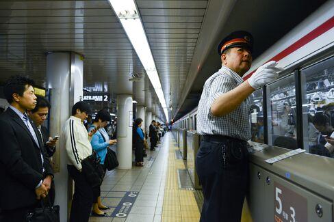 Takashi Arai, a Tokyo Metro Co. employee, gestures as he works on the platform of the Marunouchi subway line at Shinjuku station in Tokyo. Photographer:  Noriko Hayashi/Bloomberg