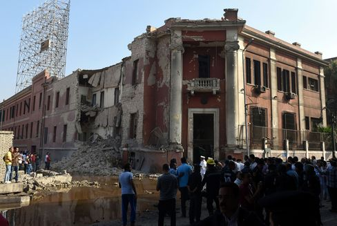 People look at the damaged Italian consulate in Cairo