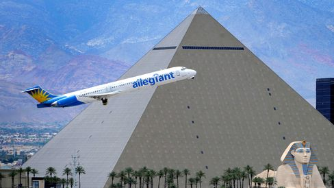 An Allegiant Air jetliner flies by the Luxor Resort and Casino after taking off from McCarran International Airport in Las Vegas on May 9, 2013.