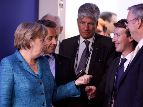 Mark Zuckerberg, founder of Facebook Inc. meets Angela Merkel, Germany's chancellor as they arrive for the internet session of the Group of Eight summit in Deauville, France, on Thursday, May 26, 2011.