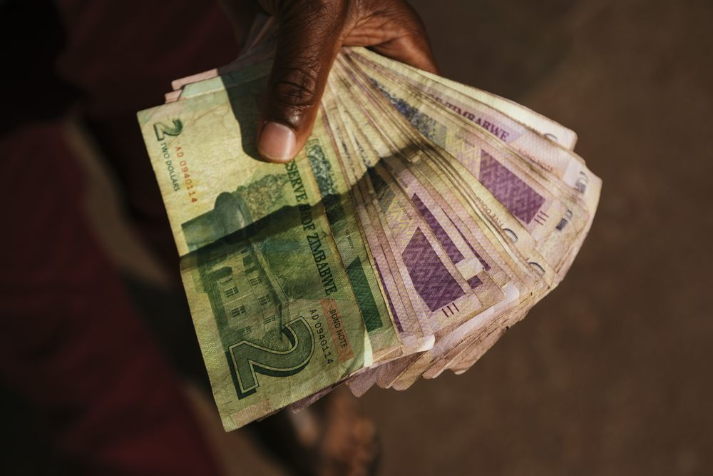 A Man Holds Zimbabwean Dollar Bond Banknotes
