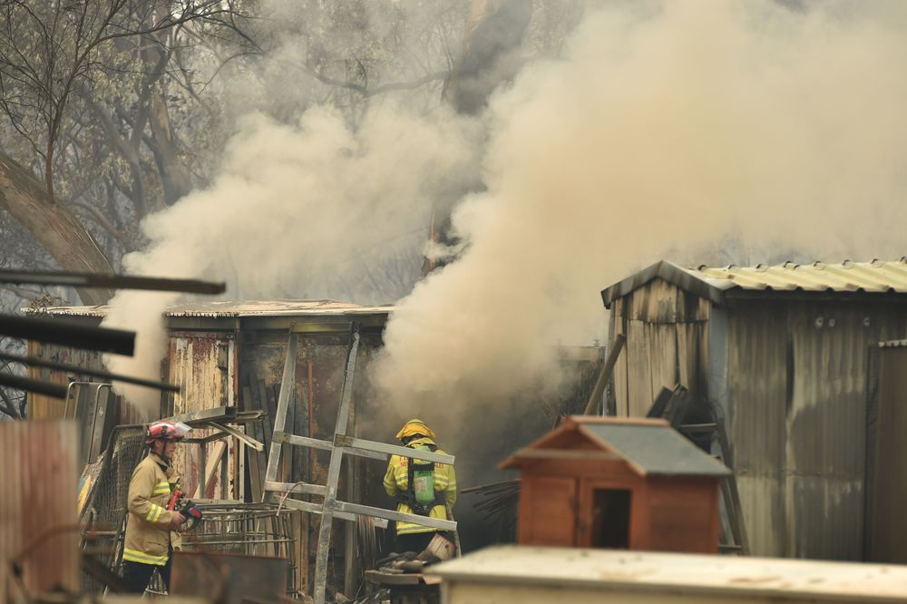 Firefighters tend to burning property caused by bushfires in Bargo on Dec.  21.